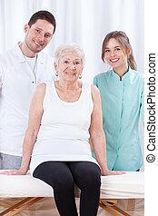 Una anciana con sus fisioterapeutas
