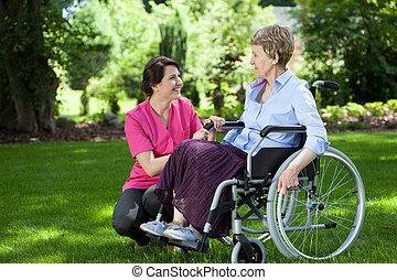 Una anciana en silla de ruedas con cuidadora