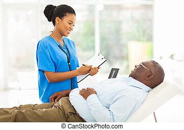 Una doctora africana consultando pacientes mayores