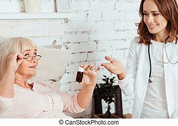 Una doctora alegre visitando a su paciente en casa