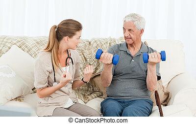 Una enfermera encantadora ayudando a su paciente a hacer ejercicios