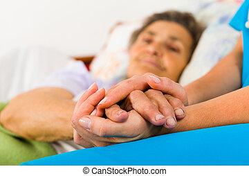 Una enfermera que se toma de la mano