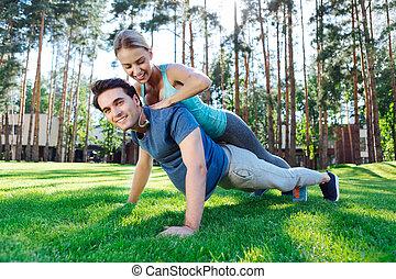 Una joven alegre ayudando a su novio a hacer flexiones