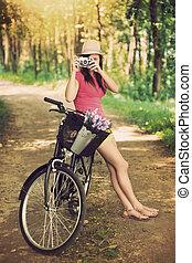 Una joven en bicicleta fotografiando la naturaleza