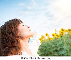 Una joven feliz en el campo de primavera de girasol
