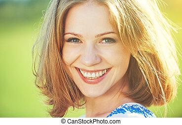 Una joven feliz riendo y sonriendo en la naturaleza
