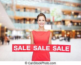 Una joven sonriente vestida con un letrero rojo