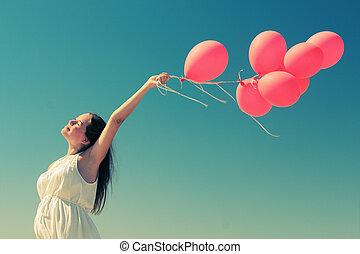 Una joven sosteniendo globos rojos