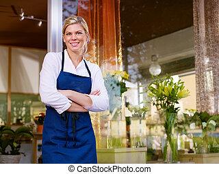 Una joven y bonita mujer trabajando como florista en la tienda y sonriendo
