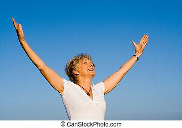 Una mujer cristiana feliz con brazos levantados de fe y alabanza
