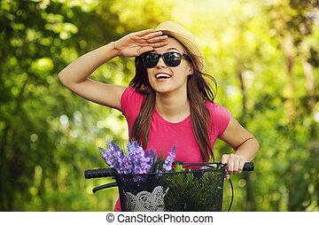 Una mujer feliz con una bicicleta mirando algo