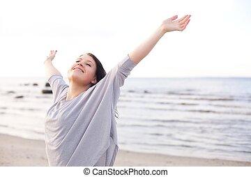 Una mujer feliz estirando sus brazos para disfrutar de la naturaleza