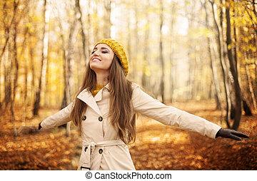 Una mujer joven disfrutando de la naturaleza en otoño