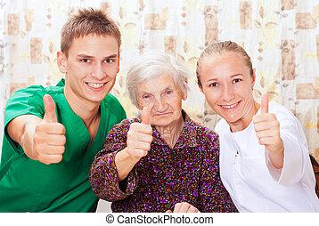 Una mujer mayor con los médicos jóvenes