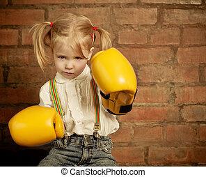 Una niña con guantes amarillos sobre la pared de ladrillos