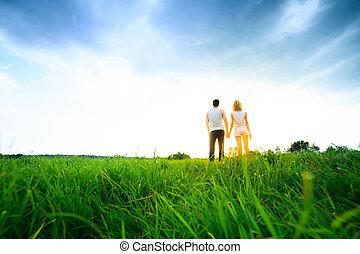 Una pareja caminando por el campo y tomandose de la mano