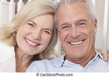 Una pareja de hombres y mujeres felices sonriendo en casa