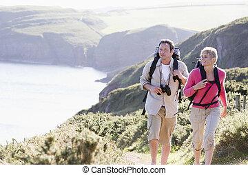 Una pareja en el precipicio, caminando y sonriendo