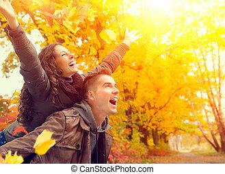 Una pareja feliz en el parque de otoño. Caída. Familia divirtiéndose al aire libre