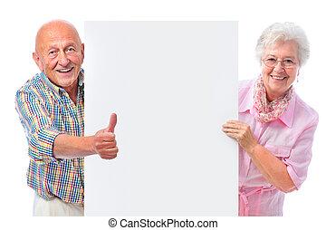 Una pareja feliz sonriendo con una tabla en blanco