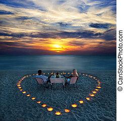 Una pareja joven comparte una cena romántica en la playa