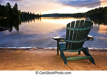 Una silla de madera al atardecer en la playa